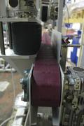 Совмещенный пластинчатый и ленточный конвейеры для нанесения этикеток на пластиковые контейнеры. Пластины конвейера в движении